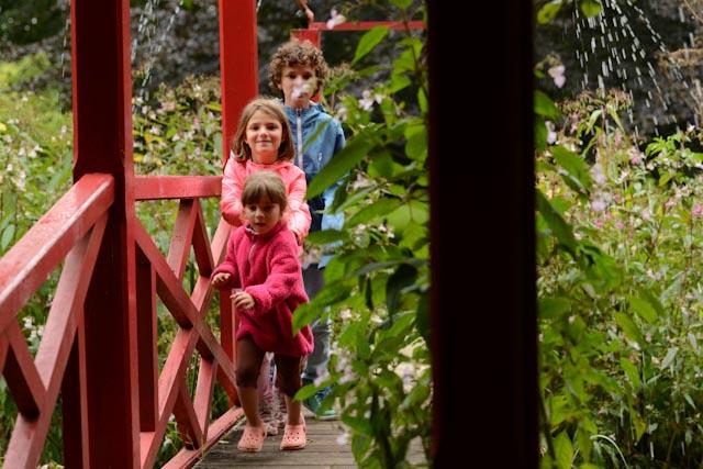 Trois enfants qui courent sur un pont chinois rouge en bois.