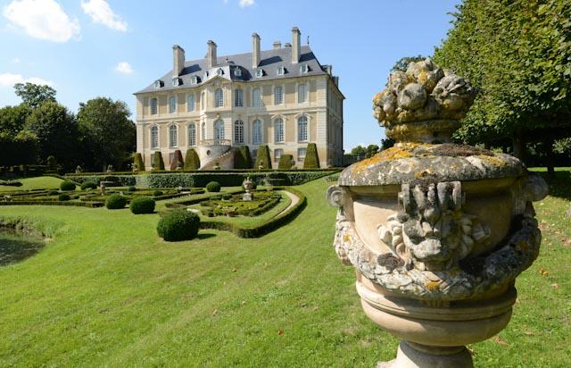 La façade arrière du château de Vendeuvre est soulignée par un parterre de buis taillé. En premier plan un vase de pierre...