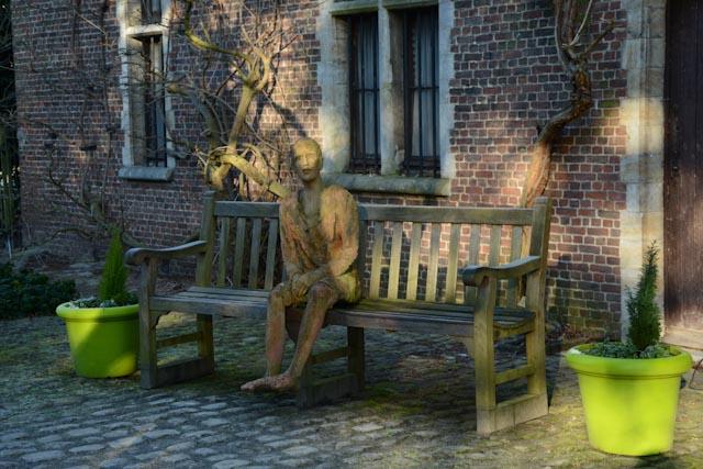 Entrée du jardin botanique de Meise : l'ancienne ferme, logement du régisseur: un homme d'argile attend assis sur un bac de bois.