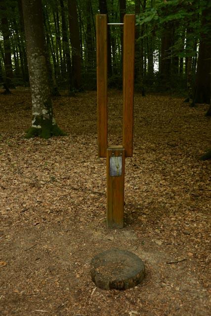 """Instrument de mesure pour évaluer la hauteur d'un arbre : un poteau en bois surmonté d'un """"U"""" toujours en bois"""