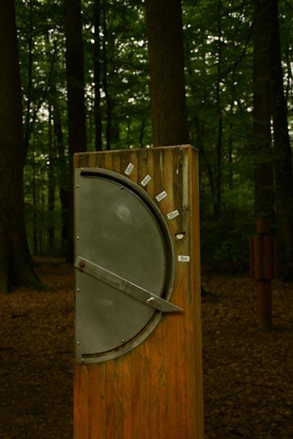 Instrument permantant d'évaluer la hauteur des arbre : une planche de bois verticale garnie d'un cadran gradué et d'une tige métallique mobile.